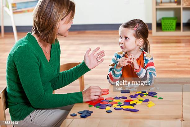Preschool girl listening to teacher in classroom