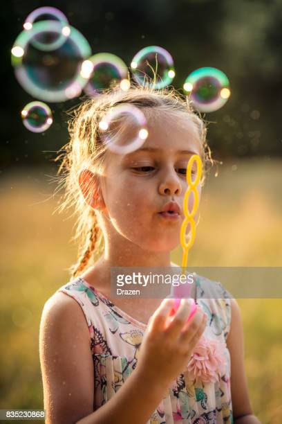 Preschool girl playing in park with bubble wand