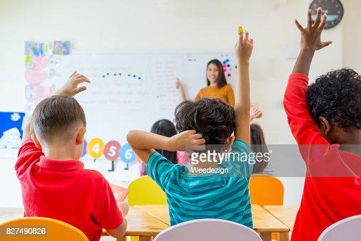 Preschool kid raise arm up to answer teacher question on whiteboard in classroom,Kindergarten education concept : Foto de stock