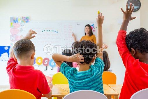 Preschool kid raise arm up to answer teacher question on whiteboard in classroom,Kindergarten education concept : Stock Photo