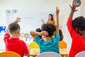 Preschool kid raise arm up to answer teacher question on whiteboard in classroom,Kindergarten education concept.