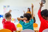 Preschool kid raise arm up to answer teacher question on whiteboard in classroom,Kindergarten education concept.