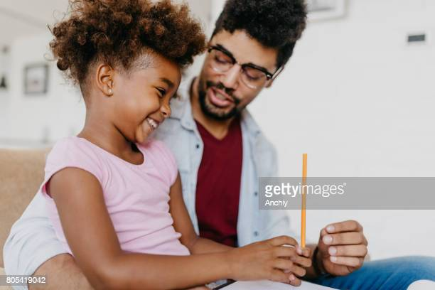 Preschool kid with beautiful hair sitting at father's lap