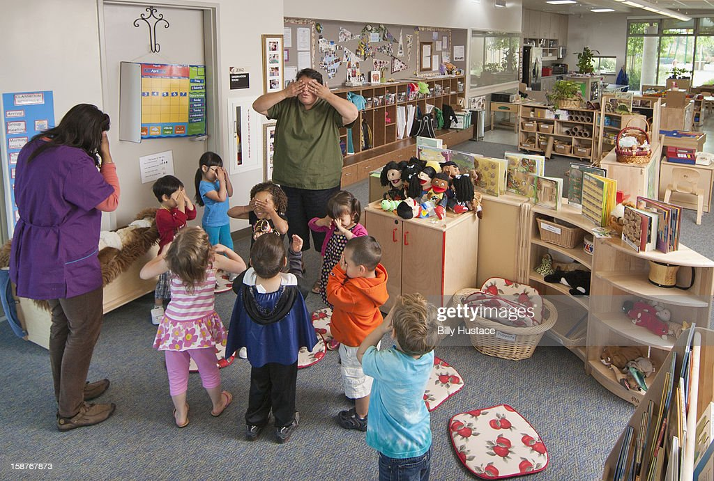 Preschool students and teacher in play activity : Stock Photo