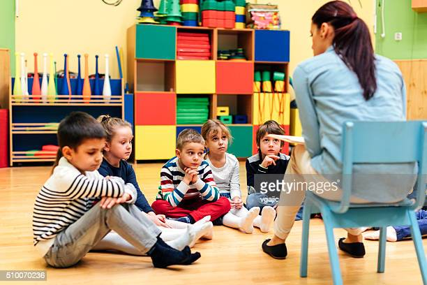 Preschool teacher and children in classroom