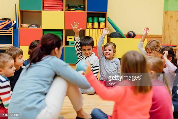 Professor e as crianças em idade pré-escolar em sala de aula