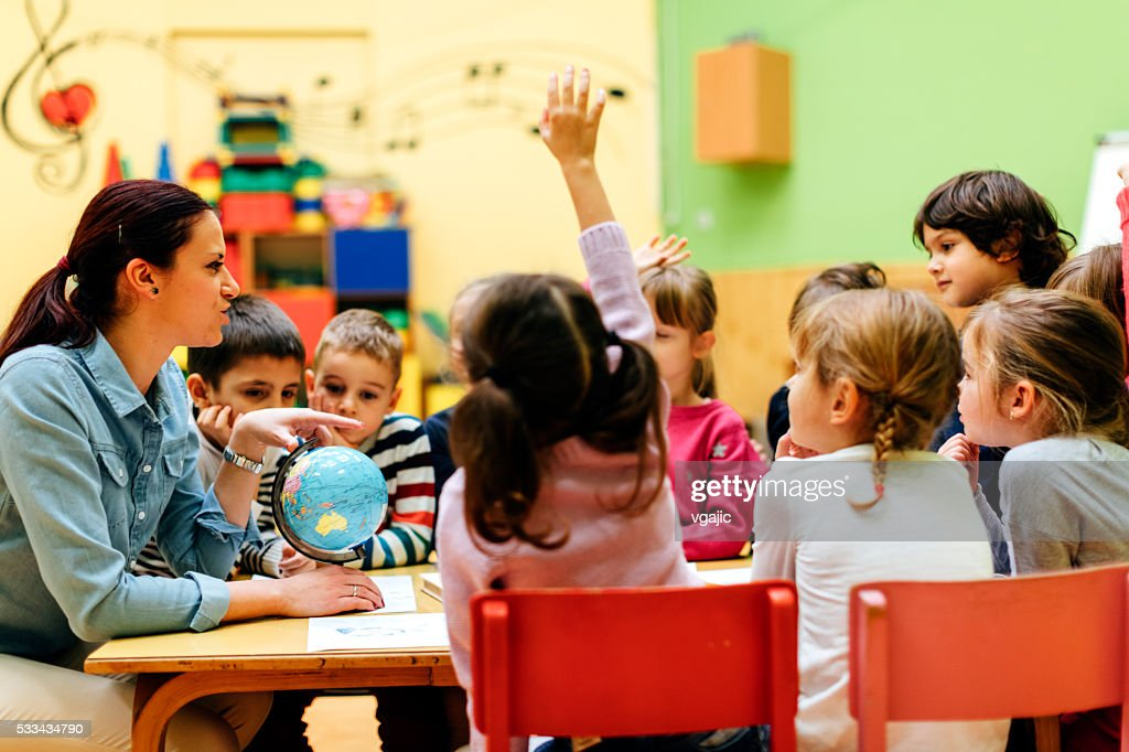 Preschool teacher and children in classroom : Stock Photo
