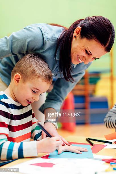 Preschool teacher assisting to cute boy in classroom
