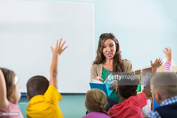 Preschool teacher, children raising hands in class
