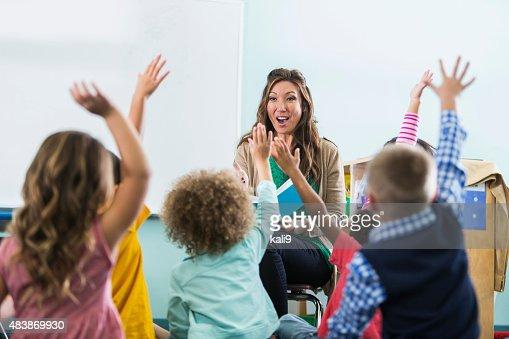 Preschool teacher, children raising hands in class