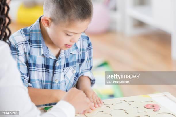 Preschool teacher helps student with number puzzle