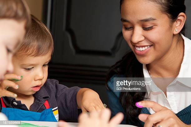 Garde d'enfants d'âge préscolaire enseignant ou Travailleur aidant enfants, peinture avec les doigts