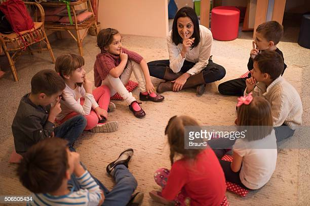 Preschool teacher playing leisure games with group of children.