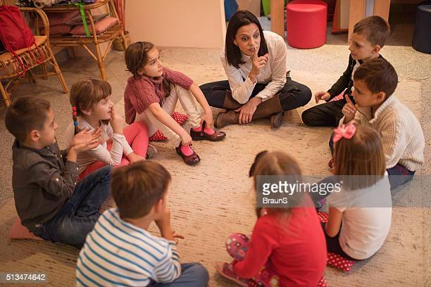 Preschool teacher playing leisure games with small kids in kindergarten.
