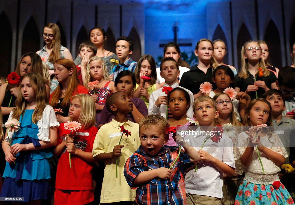 Preschooler Keltin Marazzi (C) stands on stage with other school children during the Oklahoma Strong memorial service held to honor victims of the recent deadly tornado at the First Baptist Church on May 26, 2013 in Moore, Oklahoma. The tornado of EF5 strength and two miles wide touched down May 20 killing at least 24 people and leaving behind extensive damage to homes and businesses. U.S. President Barack Obama visited the area Sunday and promised federal aid to supplement state and local recovery efforts.