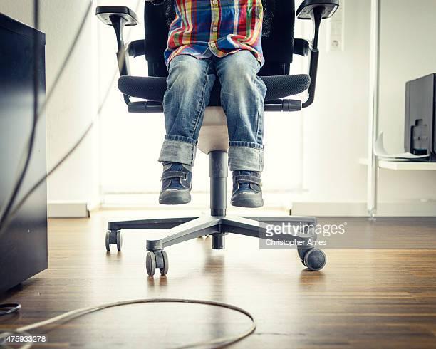 Bambino prescolare seduto alla scrivania di ufficio adulti, vista dei piedi