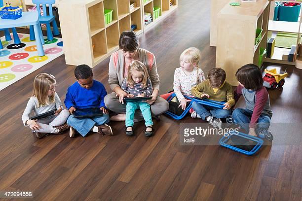Preschoolers und Lehrer mit digitalen Tablet in Klasse