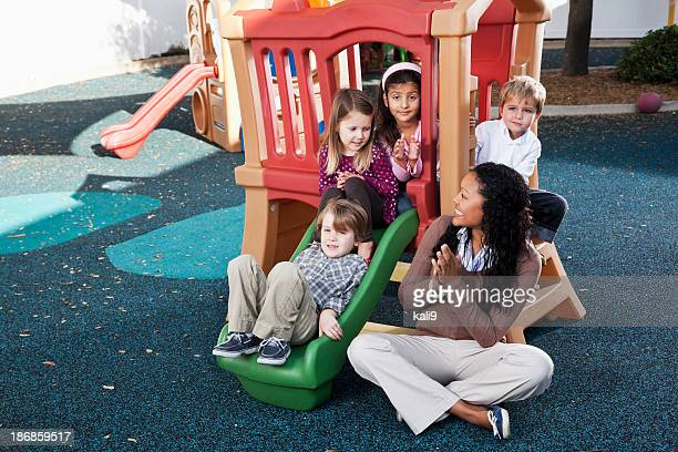 Preschoolers at daycare on playground with teacher