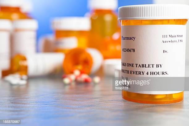 Prescription drugs. Many pill bottles on table. Spilling capsules. Medicine.