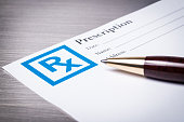 Closeup of a prescription form with a pen on a stainless steel background