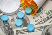 Pills spilling out of a prescription bottle on 100 dollar paper currency
