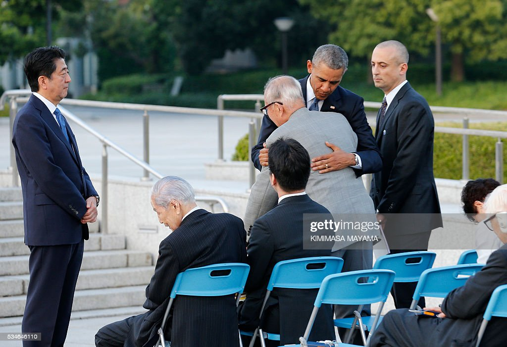 US Presdent Barack Obama (2nd R) comforts A-bomb survivor Shigeaki Mori (C) as Japanese Prime Minister Shinzo Abe (L) looks on after laying a wreath in front of the cenotaph to offer a prayer for victims of the atomic bombing in 1945 at the Hiroshima Peace Memorial Park in Hiroshima on May 27, 2016. Obama on May 27 paid moving tribute to victims of the world's first nuclear attack. MAYAMA