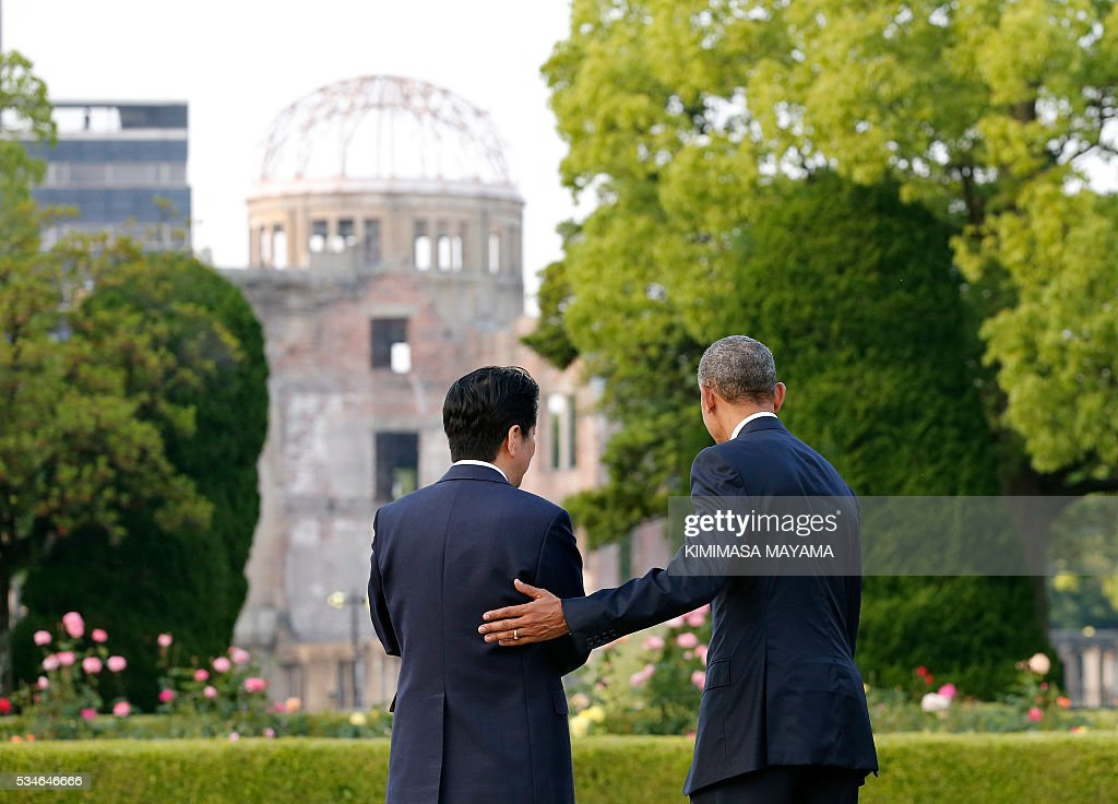 US Presdent Barack Obama puts his hand on the shoulder of Japanese Prime Minister Shinzo Abe (L) after laying a wreath in front of a cenotaph to offer a prayer for victims of the atomic bombing in 1945 at the Hiroshima Peace Memorial Park in Hiroshima on May 27, 2016. Obama on May 27 paid moving tribute to victims of the world's first nuclear attack. MAYAMA