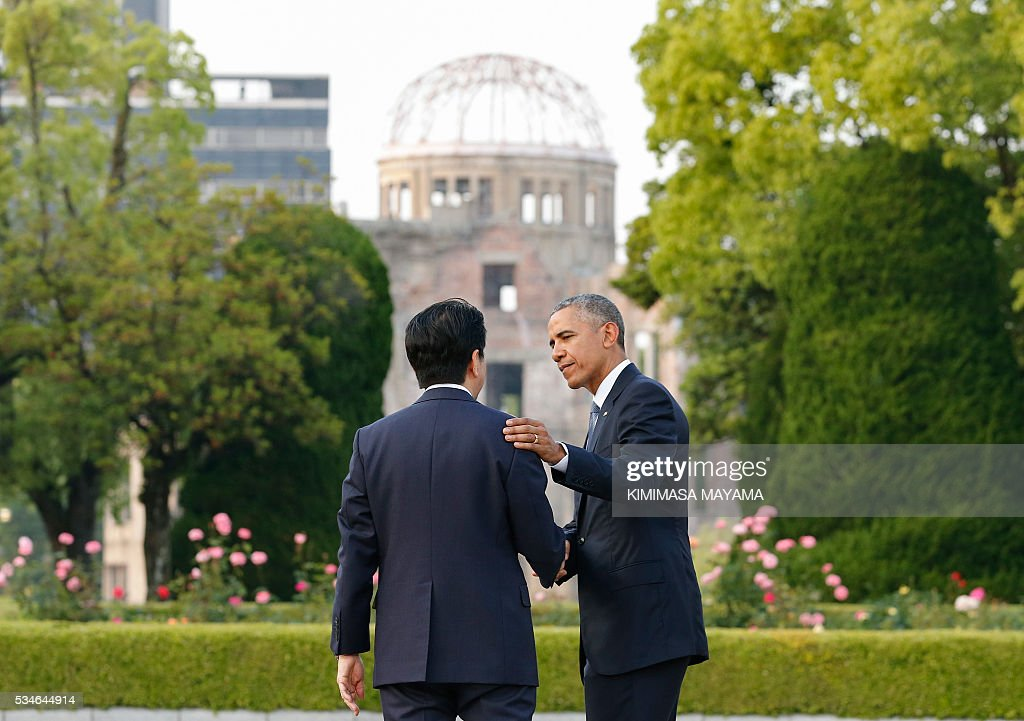 US Presdent Barack Obama (R) shakes hands with Japanese Prime Minister Shinzo Abe (L) after laying a wreath in front of the cenotaph to offer a prayer for victims of the atomic bombing in 1945 at Hiroshima Peace Memorial Park in Hiroshima on May 27, 2016. Obama on May 27 paid moving tribute to victims of the world's first nuclear attack. MAYAMA