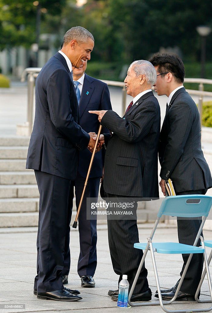 US Presdent Barack Obama (L) talks with 91-year-old A-bomb survivor Sunao Tsuboi (C) as Japanese Prime Minister Shinzo Abe (behind L) looks on, after laying a wreath in front of a cenotaph to offer a prayer for victims of the atomic bombing in 1945 at the Hiroshima Peace Memorial Park in Hiroshima on May 27, 2016. Obama on May 27 paid moving tribute to victims of the world's first nuclear attack. MAYAMA