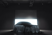 Presentation of the car covered with black cloth on dark illuminated background. 3d rendering