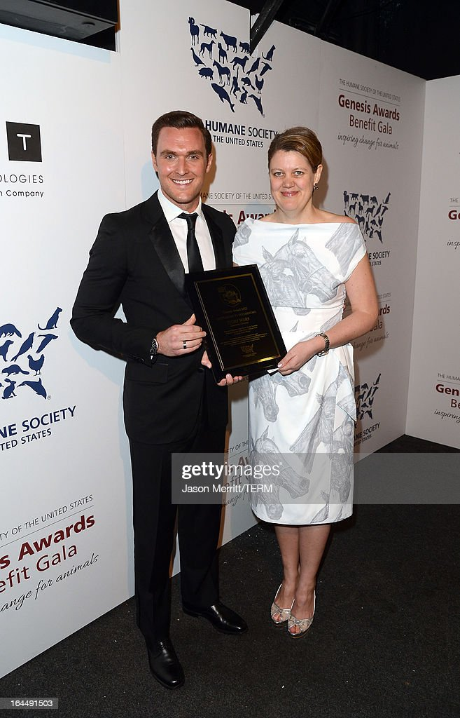 Presenter actor Owain Yeoman and producer/director Charlotte Scott pose backstage with the Outstanding TV Documentary award at The Humane Society of the United States 2013 Genesis Awards Benefit Gala at The Beverly Hilton Hotel on March 23, 2013 in Los Angeles, California.