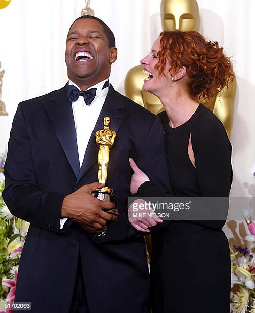 Presenter actress Julia Roberts laughs with US actor Denzel Washington who holds his Oscar for best actor in a leading role for his portrayal of...