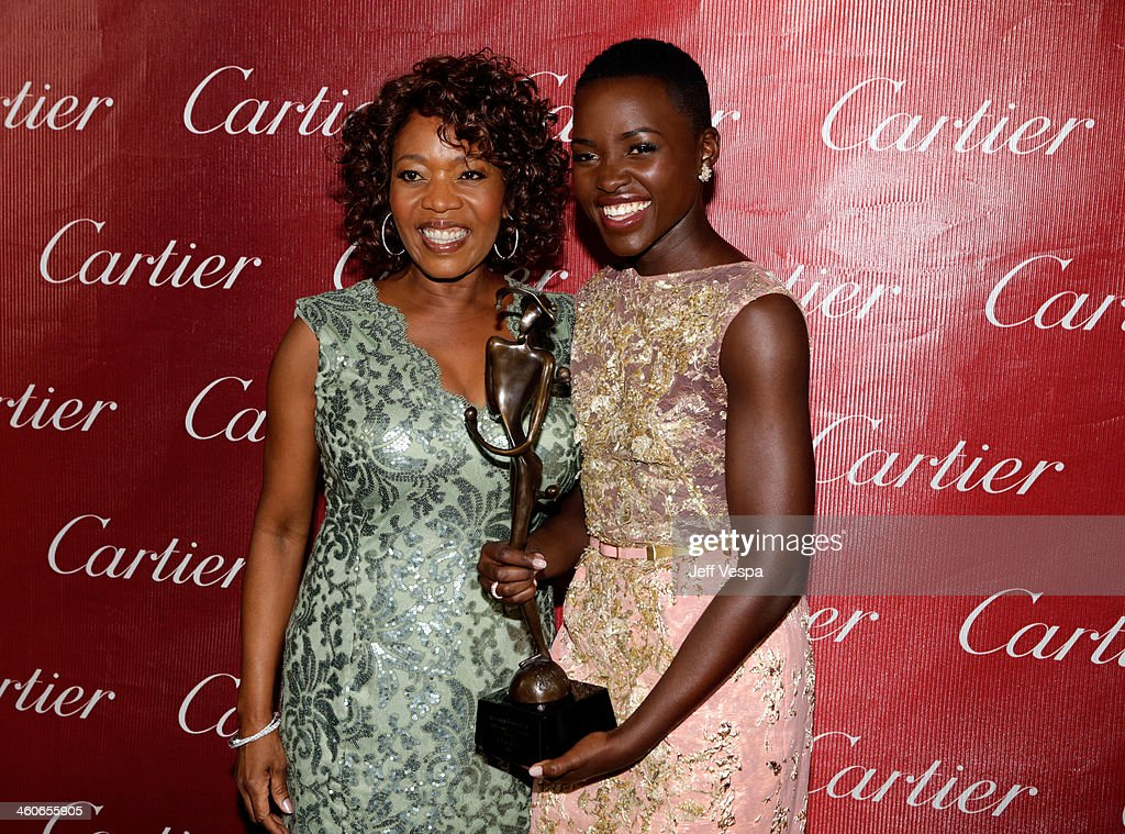 Presenter Alfre Woodard and actress Lupita Nyong'o pose with the Breakthrough Performance Award for '12 Years A Slave' backstage during the 25th...