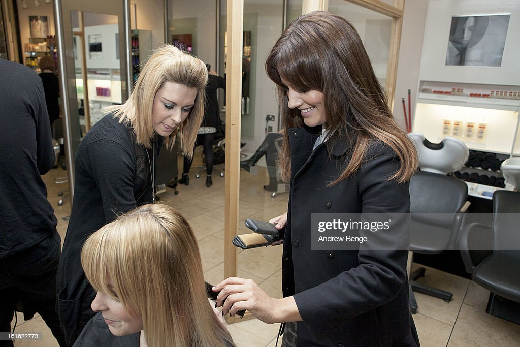 TV Presenter Caroline Flack styles the hair of a customer at Regis Salons in Manchester at The Trafford Centre on February 13, 2013 in Manchester, England.