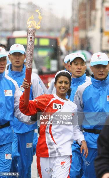TV presenter Connie Huq carries the Olmypic torch during its relay journey across London on its way to the lighting of the Olympic cauldron at the O2...