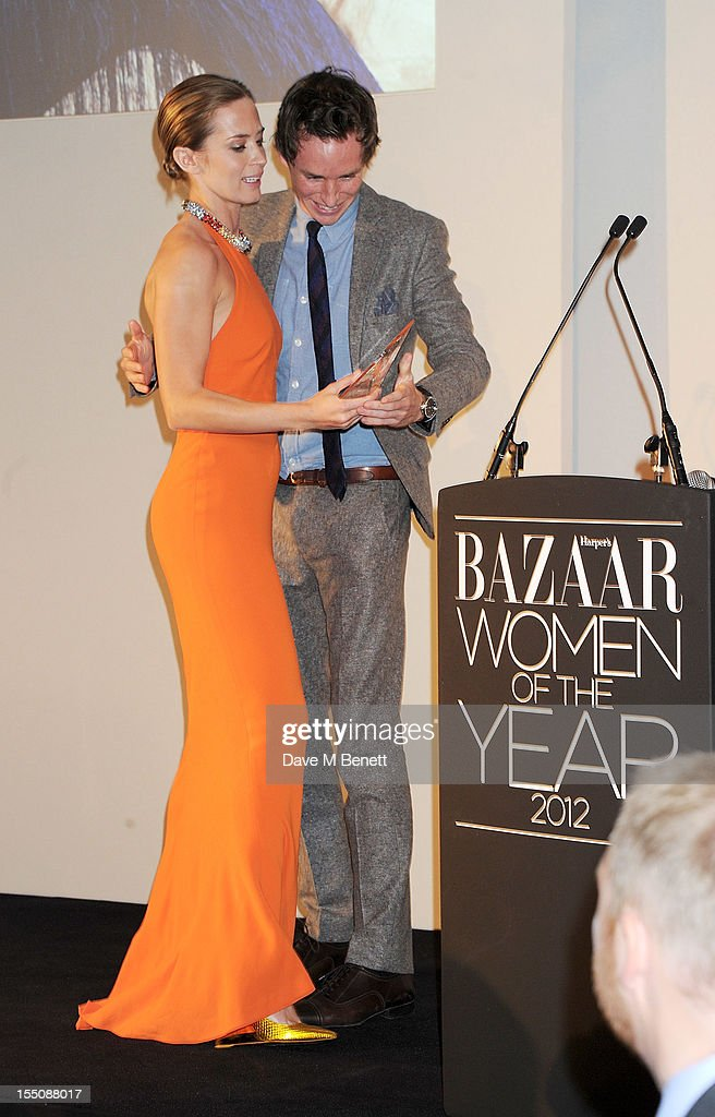 (MANDATORY CREDIT PHOTO BY DAVE M BENETT/GETTY IMAGES REQUIRED) Presenter Eddie Redmayne (R) presents actress Emily Blunt with the British Actress of the Year award at the Harper's Bazaar Women of the Year Awards 2012, in association with Estee Lauder, Harrods and Tiffany & Co., at Claridge's Hotel on October 31, 2012 in London, England.