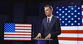 Public speaker or presenter in front of American flag standing at a small rostrum speaking and gesturing emphatically with his hands.
