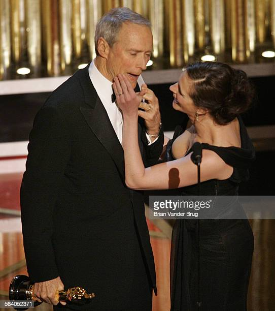 Presenter Julia Roberts wipes her lipstick kiss off of Clint Eastwood's face as he accepts his the Oscar for best director for his film 'Million...