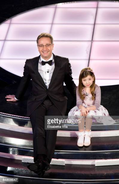 Presenter Paolo Bonolis sits onstage with an unidentified girl on opening night of the 59th San Remo Song Festival at the Ariston Theatre on February...
