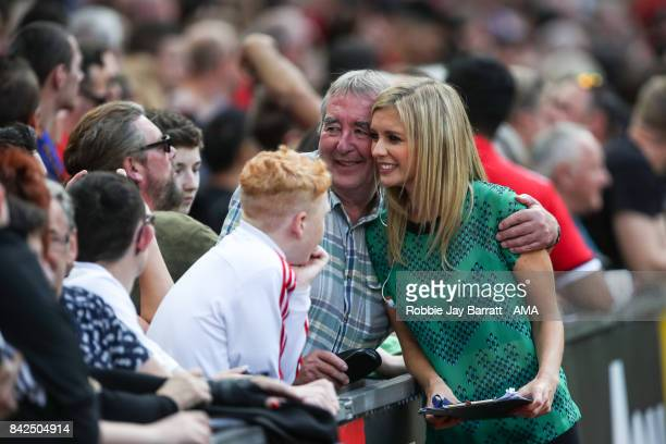Presenter Rachel Riley has a photo with a fan during the match between Manchester United Legends and FC Barcelona Legends at Old Trafford on...