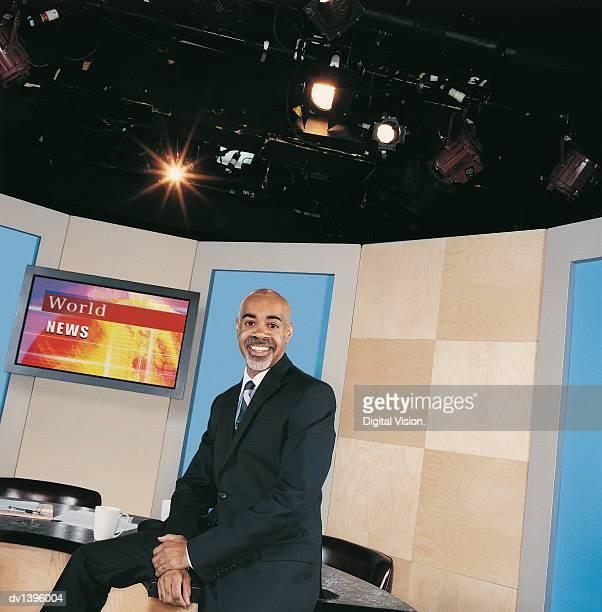 TV Presenter Sitting on a Desk in a TV Studio