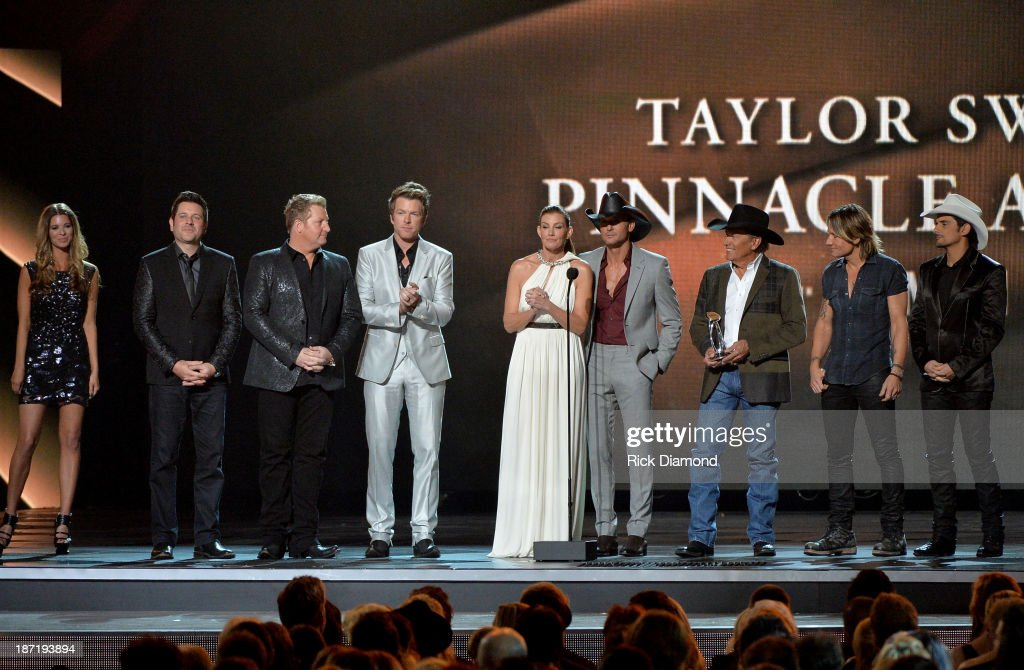 Presenters <a gi-track='captionPersonalityLinkClicked' href=/galleries/search?phrase=Jay+DeMarcus&family=editorial&specificpeople=224578 ng-click='$event.stopPropagation()'>Jay DeMarcus</a>, Joe Don Rooney and Gary LeVox of Rascall Flatts, <a gi-track='captionPersonalityLinkClicked' href=/galleries/search?phrase=Faith+Hill&family=editorial&specificpeople=175933 ng-click='$event.stopPropagation()'>Faith Hill</a>, <a gi-track='captionPersonalityLinkClicked' href=/galleries/search?phrase=Tim+McGraw&family=editorial&specificpeople=202845 ng-click='$event.stopPropagation()'>Tim McGraw</a>, <a gi-track='captionPersonalityLinkClicked' href=/galleries/search?phrase=George+Strait&family=editorial&specificpeople=234588 ng-click='$event.stopPropagation()'>George Strait</a>, <a gi-track='captionPersonalityLinkClicked' href=/galleries/search?phrase=Keith+Urban&family=editorial&specificpeople=202997 ng-click='$event.stopPropagation()'>Keith Urban</a> and <a gi-track='captionPersonalityLinkClicked' href=/galleries/search?phrase=Brad+Paisley&family=editorial&specificpeople=206616 ng-click='$event.stopPropagation()'>Brad Paisley</a> present the Pinnicle Award during the 47th annual CMA Awards at the Bridgestone Arena on November 6, 2013 in Nashville, Tennessee.