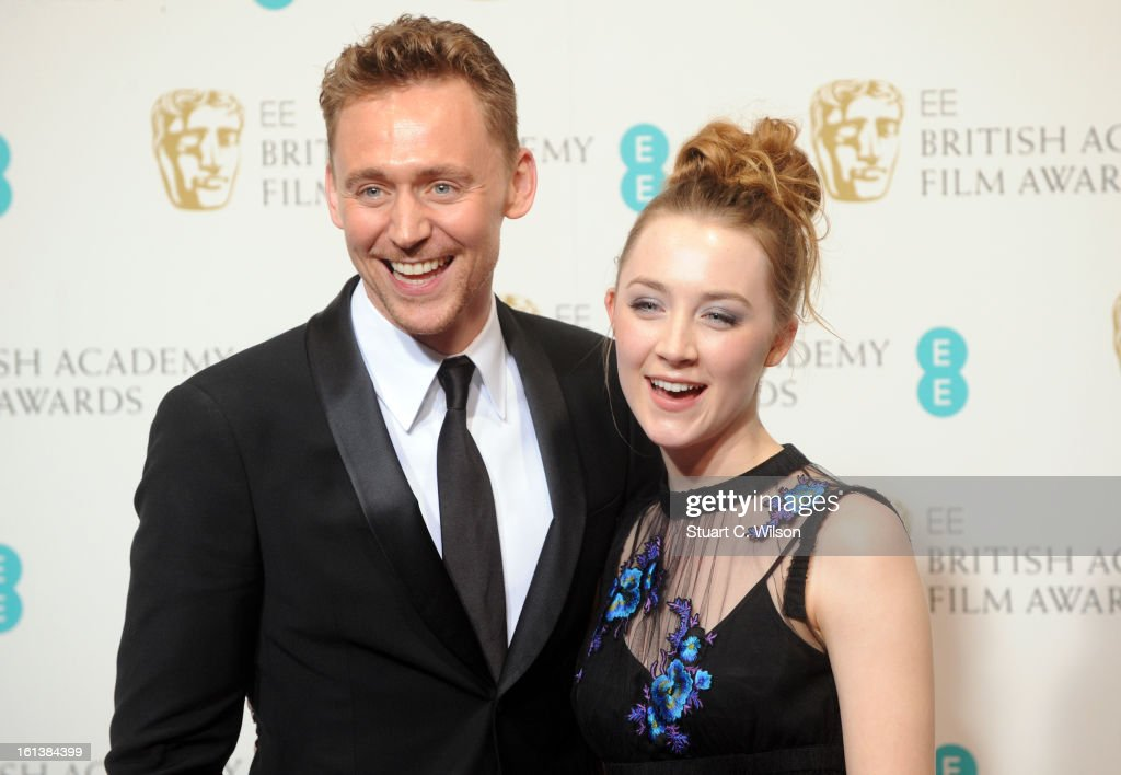 Presenters Tom Hiddleston and Saoirse Ronan pose in the press room at the EE British Academy Film Awards at The Royal Opera House on February 10, 2013 in London, England.