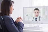 Shot of a smartly dressed woman having an on-line video conversation with a medical doctor