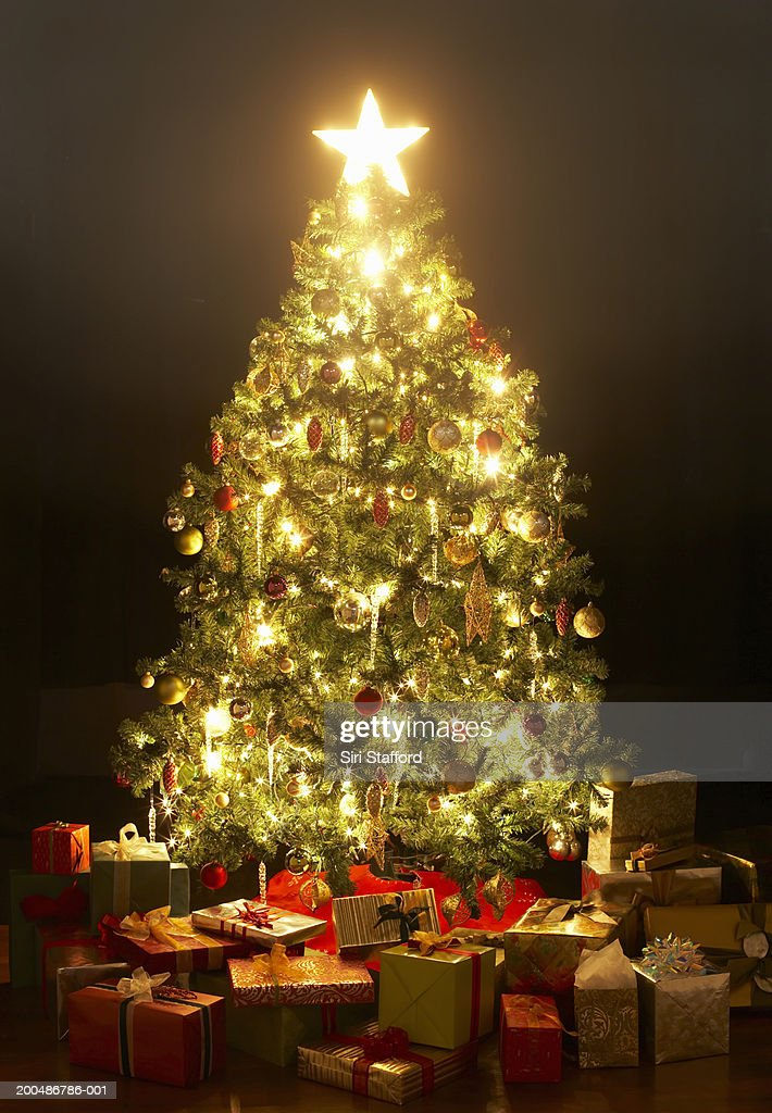 Presents around lit Christmas tree with star