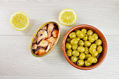 Tin of  preserved octopus in sauce and olives on a table on rustic wooden table
