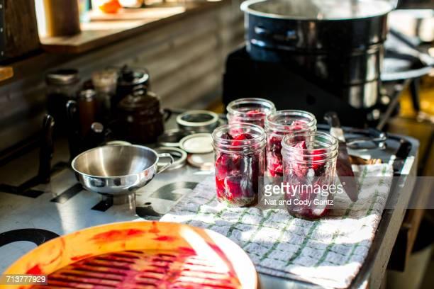 Preserves jars of beetroot on tea towel in kitchen
