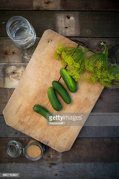 Preserving jar, gherkins and dill on wooden board