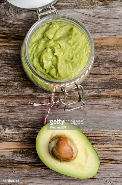 Preserving jar of avocado cream and half of avocado on wood