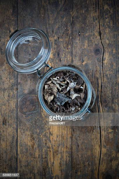 Preserving jar of dried black chanterelles, Craterellus cornucopioides, on dark wood